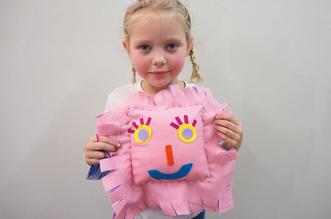 child holding a cushion she has just learnt to sew