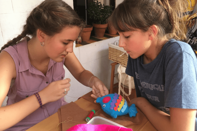 a girl sewing a soft toy with her friend